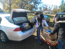 Image of volunteers unloading food supplies from a car trunk