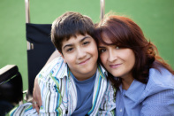 Image of boy in a wheelchair with his mother