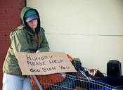 Image of homeless female with hungry sign