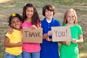 Image of 4 children holding a Thank You sign