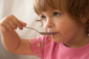 Image of child eating with spoon